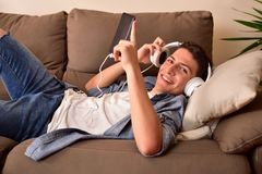 Teen lying face up on couch consuming multimedia front view Royalty Free Stock Photography
