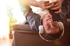 Teen lying face up on couch listening to music backlit Royalty Free Stock Photography