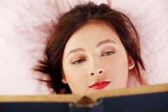 Teen lying girl reading a book. Stock Photo