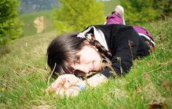 Teen lying on grass thinking. Teen lying down on the grass, looking up into sky with a thoughtful expression Royalty Free Stock Photography