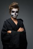 Teen with make-up of the skull in black cape Royalty Free Stock Images