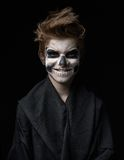Teen with make-up of skull in black cloak laughs. Teen with make-up of the skull in a black cloak laughs Stock Photography