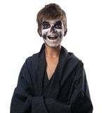 Teen with make-up of skull in black cloak laughs Stock Photo