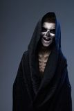 Teen with make-up of skull in black cloak laughs Stock Photography