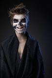 Teen with make-up of skull in black cloak laughs Royalty Free Stock Photo