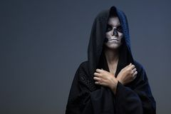 Teen with makeup closed skull hands Royalty Free Stock Photography