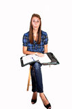 Teen making fun. Pretty teenager sitting on a chair with her notebook on her lap making fun to relax during her home work, for white background stock photos