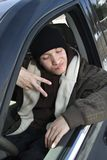 Teen making hand gesture. Caucasian male teenager making hand gesture while sitting in car Royalty Free Stock Photo