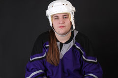 Teen male hockey player. With helmet,and jersey on a dark grey background Royalty Free Stock Photos