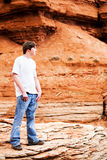 Teen male in mountains. Male teenager in mountains, standing on rock. Holes in jeans, hands in pocket, looking into distance royalty free stock images