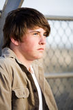 Teen male natural portrait. Teen male with natural look, unshaven, against a fence stock image
