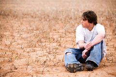 Teen male in nature. Teenager sitting outdoors in wilderness area, dry lakebed among the weeds stock photography