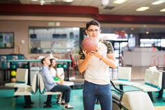 Player About To Throw A Bowling Ball In Alley. Teen male player about to throw a bowling ball in alley at club stock photography