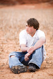 Teen male portrait. Teenager sitting amongst the weeds in a dry lakebed. Natural-looking teen, simple clothing, ripped jeans, shot in Wyoming with copyspace royalty free stock images