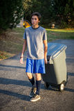Teen male - taking out the trash. Male teenager wearing blue shorts and a grey t-shirt doing family chores - taking out the trash Stock Images