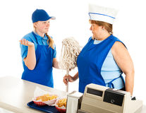 Teen Manager Bosses Adult Employee. Adult women working at a fast food job has to take orders from a teenage boss.  Isolated on white Stock Photo
