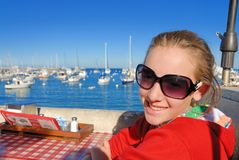 Teen by marina. Teenager sit in restaurant by marina waiting for food Stock Photography