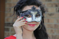 Teen Masquerade Mask. A happy teenage girl with long dark hair and red blouse wearing a sparkly masquerade mask masque Stock Photography