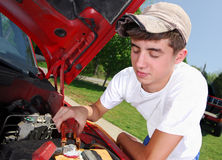 Teen mechanic. A smiling teenage boy working on a truck engine Stock Photo