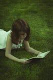 teen Menina bonita nova que lê um livro ao ar livre imagem de stock royalty free