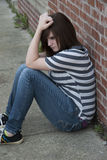 Teen Mental Health. Teenage girl sitting against brick wall in a depressed state stock photography