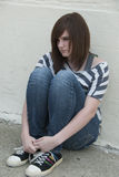 Teen Mental Health. Teenage girl sitting against brick wall in a depressed state Royalty Free Stock Photos