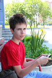 Teen messaging. Teen is sitting and messaging from his mobile phone outdoors Royalty Free Stock Photos