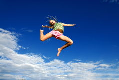 Teen in mid-jump. Teen jumping in air; against blue sky Royalty Free Stock Photo