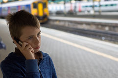 Teen on a mobile. An image of a young teenager on the phone looking worried at the train station royalty free stock photo