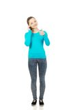 Teen with mobile phone and thumbs up. Stock Photo