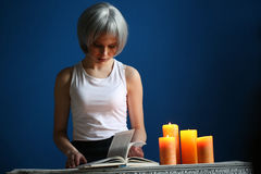 Teen model posing with book and candles. Close up. Blue background. Teen model posing with book and candles, silver wig, girl with book, high fashion look Royalty Free Stock Image
