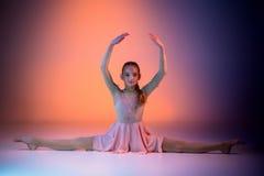 The teen modern ballet dancer. The female teen modern ballet dancer on orange studio background stock photo