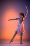 The teen modern ballet dancer. The female teen modern ballet dancer on orange studio background stock photos