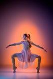 The teen modern ballet dancer. The female teen modern ballet dancer on orange studio background stock photography