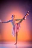 The teen modern ballet dancer. The female teen modern ballet dancer on orange studio background stock images
