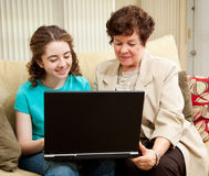 Teen and Mom Shopping Online. Teen girl and her mother shopping together on their laptop computer Stock Photography