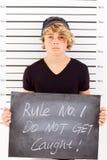 Teen mug shot. Teen boy holding a blackboard criminal mug shot Stock Images
