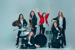 The teen music band performing in a recording studio. Teen music band performing in a recording studio. The group of girls standing together and posing at camera stock photography