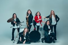 The teen music band performing in a recording studio. Teen music band performing in a recording studio. The group of girls standing together and posing at camera Royalty Free Stock Photos