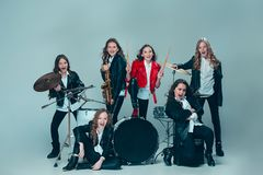 The teen music band performing in a recording studio. Teen music band performing in a recording studio. The group of girls standing together and posing at camera royalty free stock images
