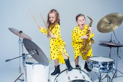 The teen music band performing in a recording studio. Teen music girls performing in a recording studio. The group of two girls standing together. Studio stock photos