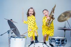 The teen music band performing in a recording studio. Teen music girls performing in a recording studio. The group of two girls standing together. Studio stock photo