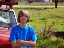Teen and Old Truck. Teen aged boy with arms crossed wearing a blue shirt standing in front of old red truck in a grassy field Royalty Free Stock Photo