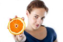 Teen with orange. Teen girl holding a sliced orange. Studio shot. Focus on the orange Stock Image