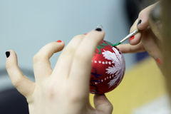 Teen paints Christmas toy Stock Photo