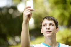 Teen with palmtop. Portrait of young man with gadget ,ambient light and silver reflection, focus on eye Royalty Free Stock Photos