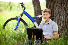 Teen in park with new laptop Stock Photos
