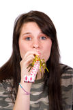 Teen party favor. Teenage girl with party favor noise maker shot over white stock image