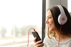 Teen passenger listening to the music traveling in a train Stock Photography