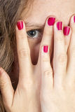 Teen Peeking thorugh fingers. A Teen Peeking thorugh fingers her fingers with red nails Royalty Free Stock Photos